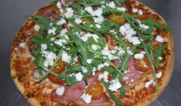 Picture of a cooked prosciutto pizza with fresh rocket leaves on top