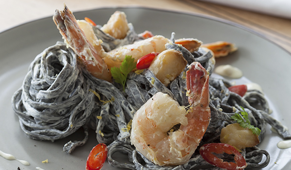 Picture of squid ink pasta with prawns and herbs.